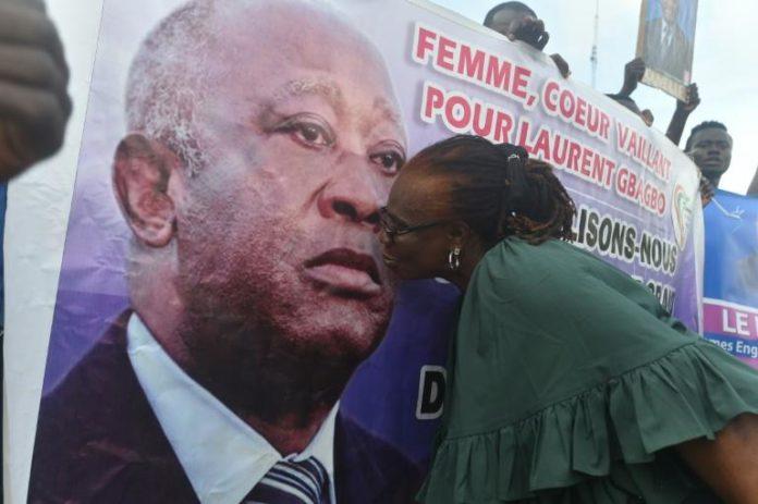Une partisane de Laurent Gbagbo vient embrasser son portrait lors d'une manifestation à Abidjan le 31 août 2020 afp.com - SIA KAMBOU