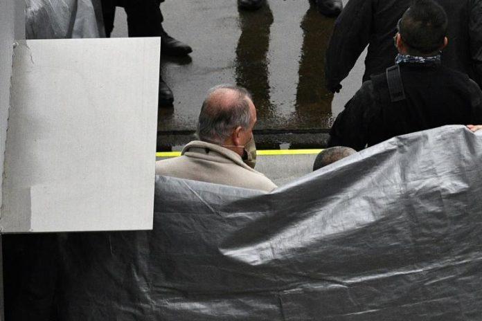 Un homme, supposé être Michael Taylor, accusé d'avoir aidé Carlos Ghosn dans sa fuite, est escorté par des policiers à son arrivée à l'aéroport de Narita, le 2 mars 2021 au Japon afp.com - Kazuhiro NOGI