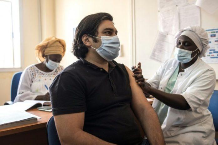 un homme reçoit une dose du vaccin AstraZeneca contre le Covid-19 dans une clinique à Ngor, un quartier de Dakar, le 2 avril 2021 afp.com - JOHN WESSELS
