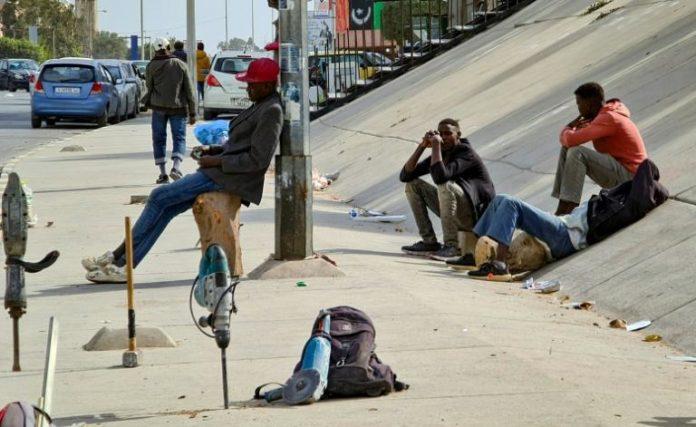 Des migrants africains attendent de trouver employeur pour un travail journalier dans la capitale libyenne Tripoli, le 6 mars 2021 afp.com - Mahmud TURKIA