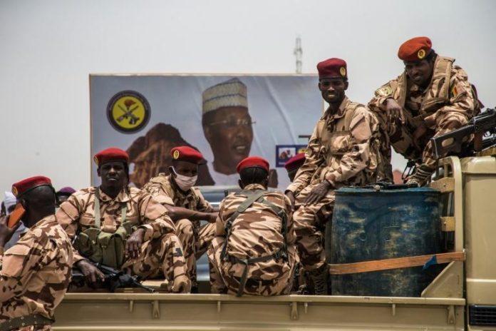 Des militaires tchadiens à bord d'un véhicule garé devant une affiche électorale en faveur du défunt président Idriss Déby Itno, à N'Djamena le 23 avril 2021 afp.com - Christophe PETIT TESSON