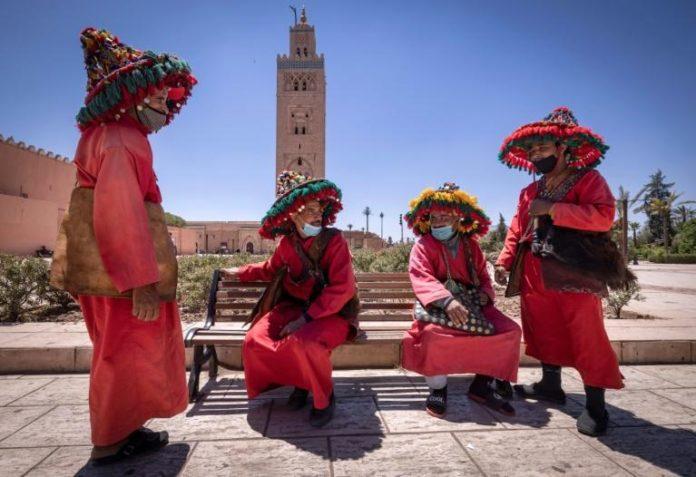 Des vendeurs d'eau à Marrakech, capitale touristique du Maroc, discutent devant une mosquée, le 6 mai 2021 afp.com - FADEL SENNA