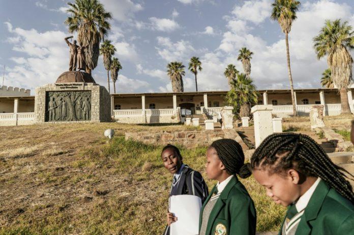 Des jeunes filles en uniforme scolaire passent devant le mémorial aux victimes du génocide commis par les colons allemands en 1904 contre les Hereros et le Namas en Namibie à Windhoek, le 20 juin 2017 afp.com - GIANLUIGI GUERCIA