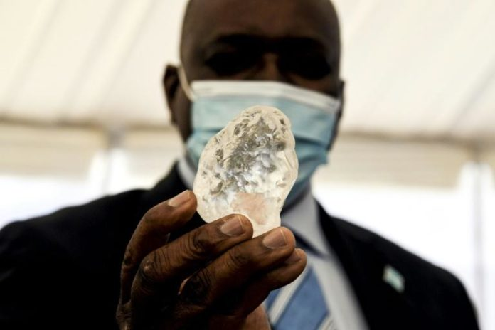 Le président botswanais Mokgweetsi Masisi tient un diamant de 1.098 carats, le troisième plus gros de ce type trouvé dans le monde, le 16 juin 2021 à Gaborone afp.com - Monirul Bhuiyan