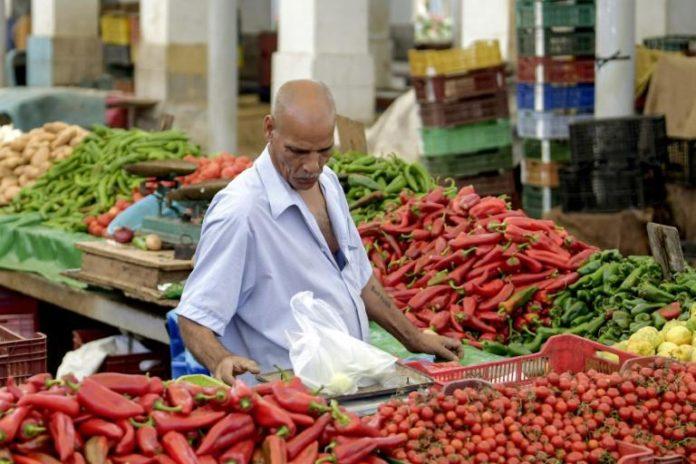 Un marchand pèse des produits sur un étal au marché populaire de Bab el-Fellah, à Tunis, le 28 juillet 2021 afp.com - FETHI BELAID