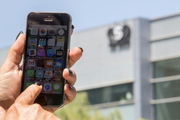 Une femme montre son téléphone devant le siège de l'entreprise NRO, qui a conçu un logiciel espion, le 28 août 2016 à Herzliya, en Israël. afp.com - JACK GUEZ