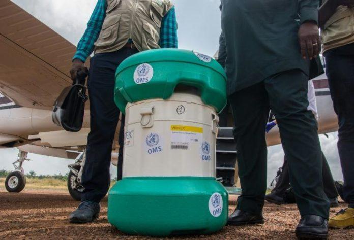 Des personnels du ministère guinéen de la Santé et de l'OMS se tiennent près d'un conteneur de doses de vaccin contre Ebola le 23 février 2021 à Guéckédou, en Guinée afp.com - CAROL VALADE