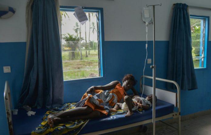 Une femme près d'un enfant ayant contracté le paludisme à Jacqueville, en Côte d'Ivoire, le 19 avril 2019 afp.com - Sia KAMBOU