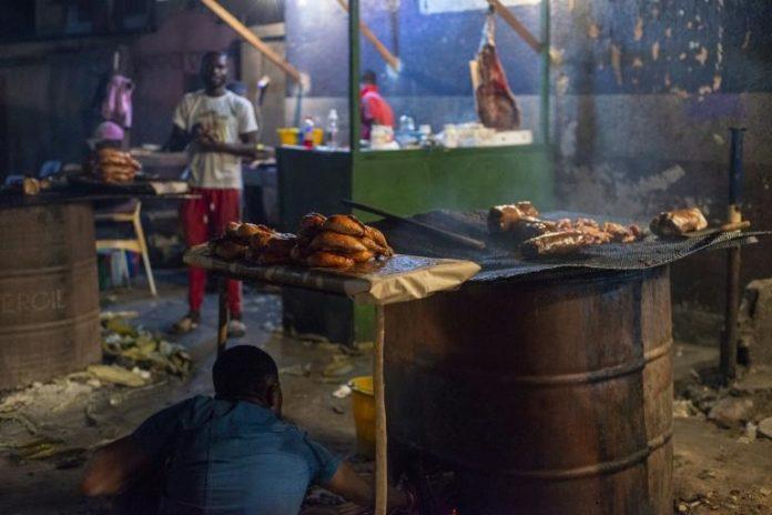Un cuisinier ajoute du bois sur un un barbecue, où des poulets sont cuits pour être vendus dans les rues de Kinshasa le 14 septembre 2021 afp.com - ARSENE MPIANA