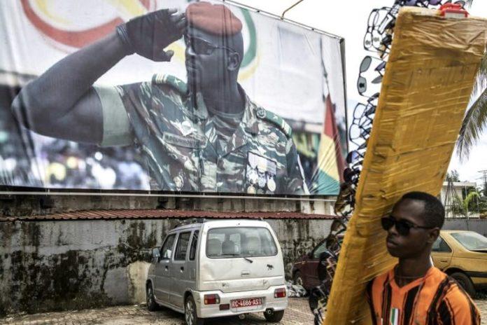 Un vendeur de lunettes passe devant une affiche géante montrant le chef de la junte guinéenne, le lieutenant-colonel Mamady Doumbouya, à l'origine du putsch contre le président Alpha Condé, à Conakry le 11 septembre 2021 afp.com - JOHN WESSELS